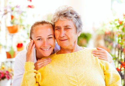 caregiver and senior woman are smiling together