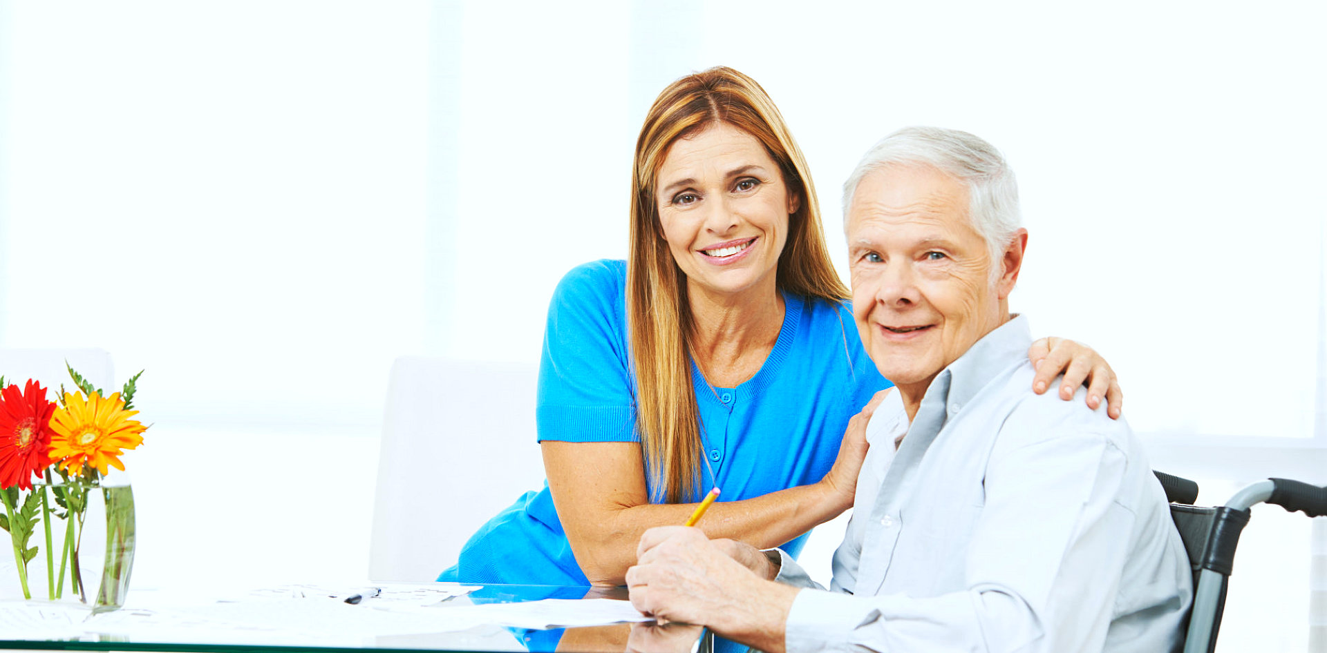 caregiver and senior man are smiling while he is writing at the paper