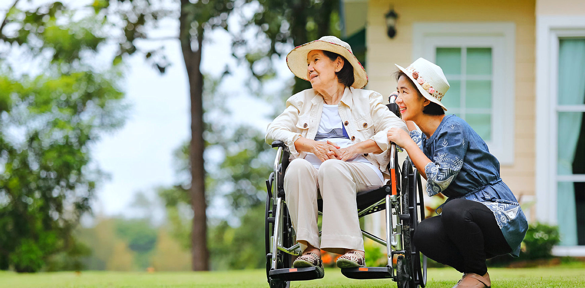 caregiver and senior woman on the wheelchair are looking outdoor